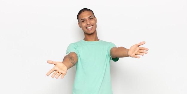 Jonge zwarte man die vrolijk lacht en een warme, vriendelijke, liefdevolle welkomstknuffel geeft, zich gelukkig en schattig voelt