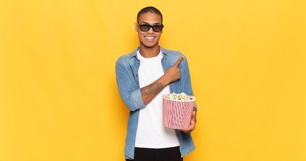 Jonge zwarte man die vrolijk lacht, zich gelukkig voelt en naar de zijkant en naar boven wijst, object in kopie ruimte toont