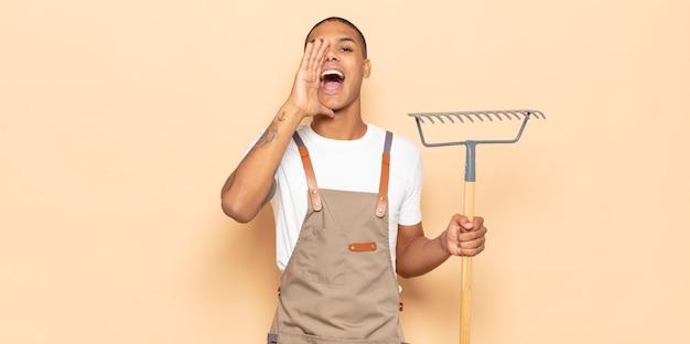 Jonge zwarte man die zich blij, opgewonden en positief voelt, een grote schreeuw geeft met de handen naast de mond, roept