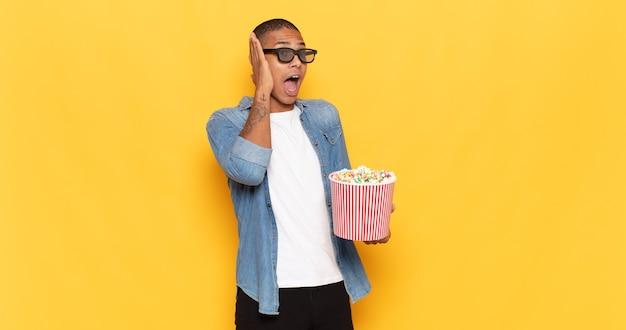 Jonge zwarte man die zich blij, opgewonden en verrast voelt, naar de zijkant kijkend met beide handen op het gezicht