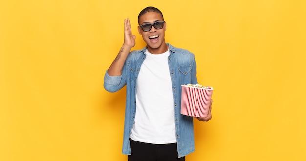 Jonge zwarte man die zich blij, opgewonden, verrast of geschokt voelt, glimlacht en verbaasd is over iets ongelooflijks Premium Foto