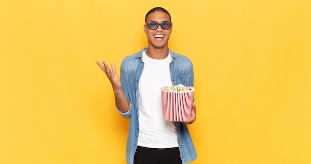 Jonge zwarte man die zich blij, verrast en opgewekt voelt, lacht met een positieve houding, een oplossing of idee realiseert