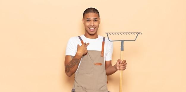 Jonge zwarte man die zich blij, verrast en trots voelt en naar zichzelf wijst met een opgewonden, verbaasde blik