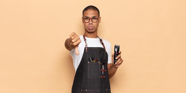 Jonge zwarte man die zich boos, boos, geïrriteerd, teleurgesteld of ontevreden voelt, duimen naar beneden toont met een serieuze blik