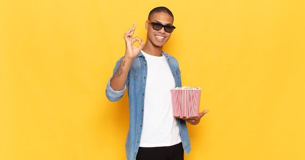 Jonge zwarte man die zich gelukkig, ontspannen en tevreden voelt, goedkeuring toont met een goed gebaar, glimlachend