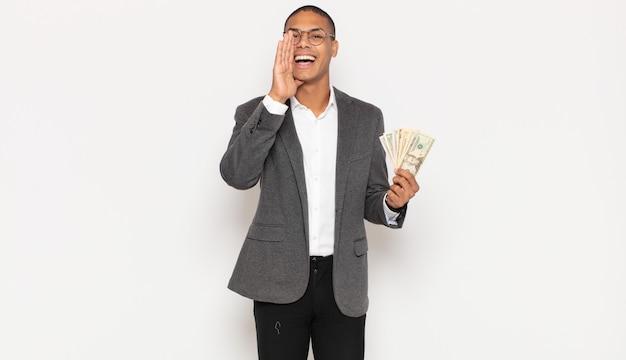 Jonge zwarte man die zich gelukkig, opgewonden en positief voelt, een grote schreeuw geeft met handen naast de mond, roept