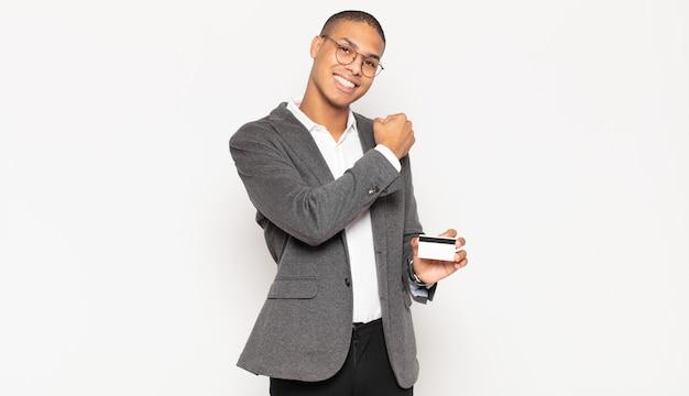 Jonge zwarte man die zich gelukkig, positief en succesvol voelt, gemotiveerd wanneer hij voor een uitdaging staat of goede resultaten viert