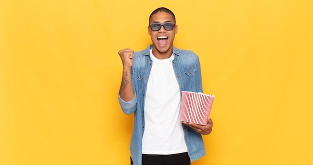 Jonge zwarte man die zich geschokt, opgewonden en gelukkig voelt, lacht en succes viert en wauw zegt!