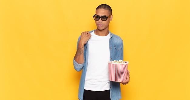 Jonge zwarte man die zich gestrest, angstig, moe en gefrustreerd voelt, de nek van het shirt trekt, gefrustreerd kijkt door het probleem