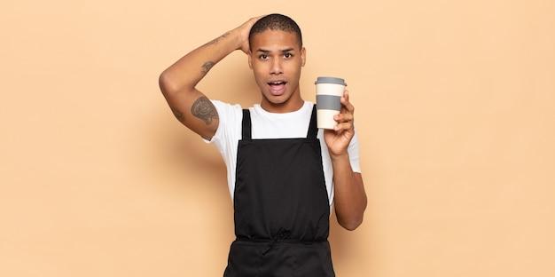 Jonge zwarte man die zich gestrest, bezorgd, angstig of bang voelt, met de handen op het hoofd, in paniek raakt bij vergissing