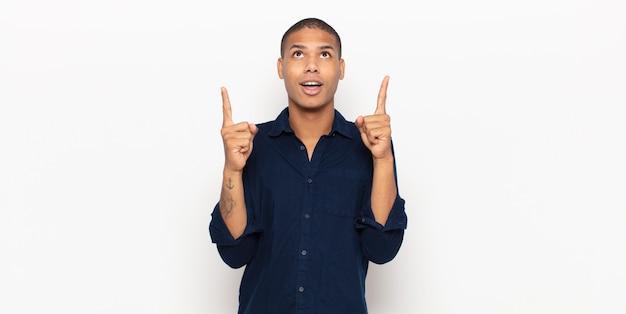 Jonge zwarte man die zich onder de indruk voelt en met open mond naar boven wijst met een geschokte en verbaasde blik
