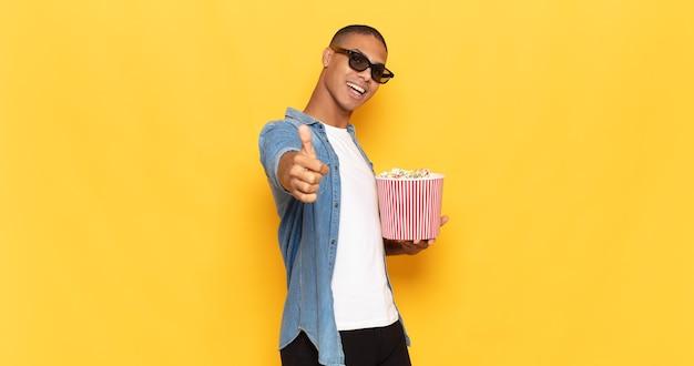 Jonge zwarte man die zich trots, zorgeloos, zelfverzekerd en gelukkig voelt en positief glimlacht met zijn duimen omhoog