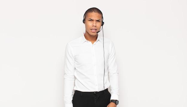 Jonge zwarte man die zich verbaasd en verward voelde, met een domme, verbijsterde uitdrukking op zoek naar iets onverwachts