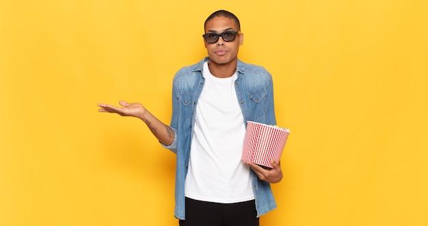 Jonge zwarte man die zich verbaasd en verward voelt, twijfelt, weegt of verschillende opties kiest met een grappige uitdrukking