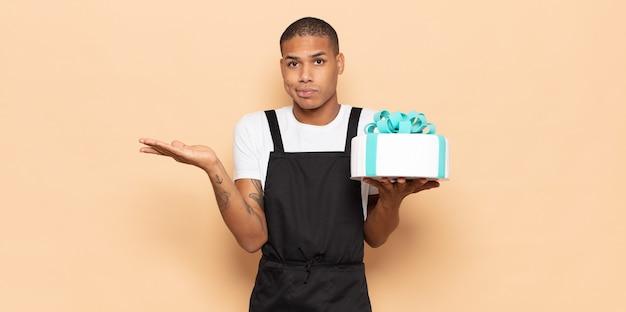 Jonge zwarte man die zich verbaasd en verward voelt, twijfelt, weegt of verschillende opties kiest met grappige uitdrukking