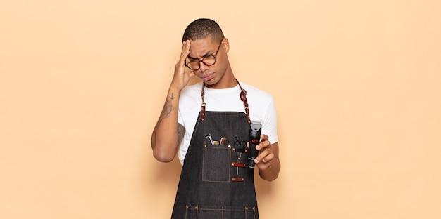 Jonge zwarte man die zich verveeld, gefrustreerd en slaperig voelt na een vermoeiende, saaie en vervelende taak, gezicht met hand vasthoudend