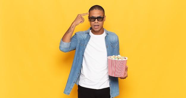 Jonge zwarte man die zich verward en verbaasd voelt, laat zien dat je gek, gek of gek bent