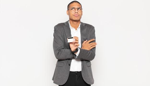 Jonge zwarte man die zijn schouders ophaalt, zich verward en onzeker voelt, twijfelt met gekruiste armen en een verbaasde blik