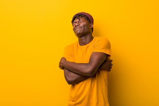 Jonge zwarte man draagt rasta's over geel knuffels zichzelf, zorgeloos en gelukkig glimlachen.