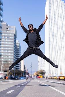 Jonge zwarte man dragen casual kleding springen in straat