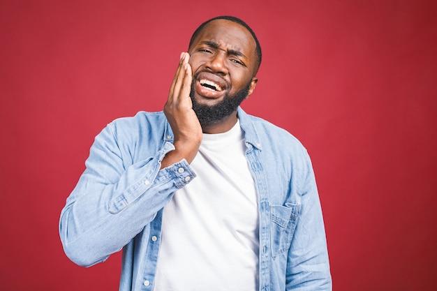 Jonge zwarte man geïsoleerd op rode achtergrond met open mond, zijn gezicht aan te raken met een vreselijke uitdrukking lijden aan gezondheidsproblemen en pijnlijke tand.