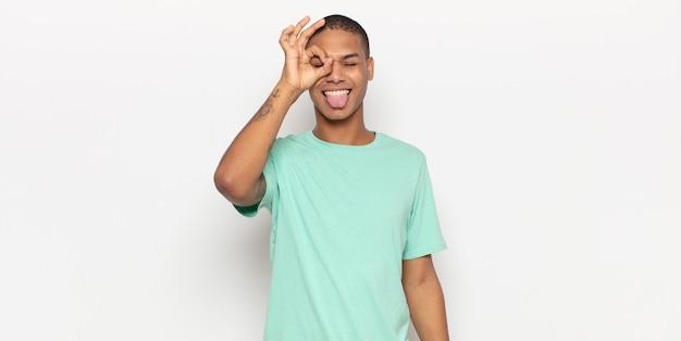 Jonge zwarte man gelukkig lachend met grappig gezicht, grapje en kijkend door kijkgaatje, geheimen bespioneren