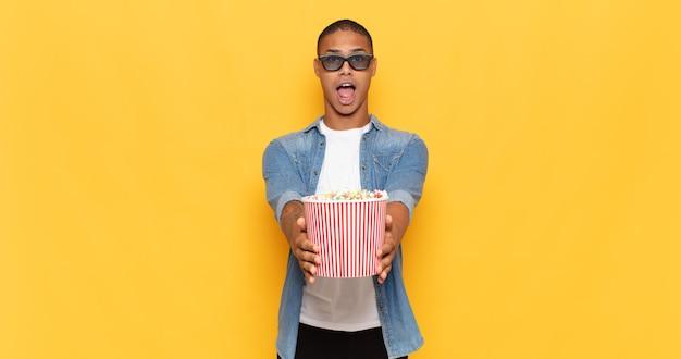 Jonge zwarte man gelukkig lachend met vriendelijke, zelfverzekerde, positieve blik, aanbieden en tonen van een object of concept