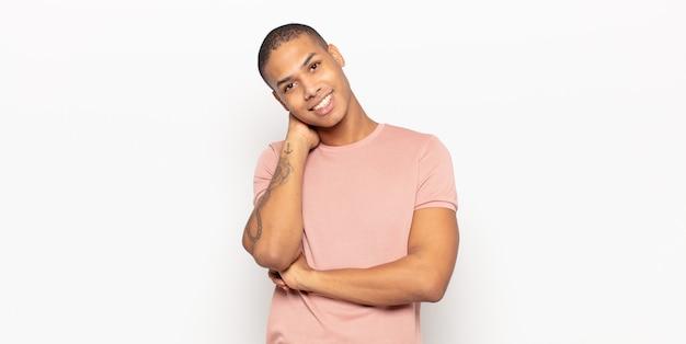 Jonge zwarte man glimlachend vrolijk en nonchalant, hand in hand met een positieve, vrolijke en zelfverzekerde blik
