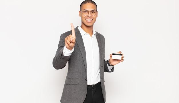 Jonge zwarte man lacht en ziet er vriendelijk uit, toont nummer één of eerste met hand naar voren, aftellend