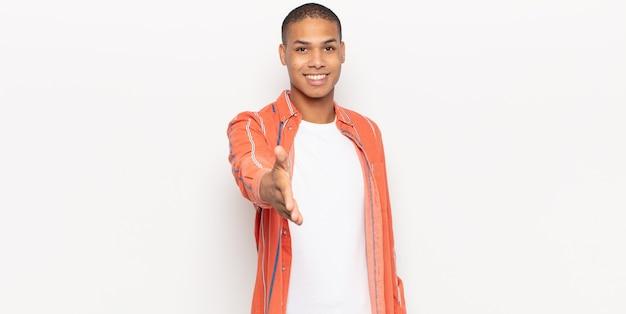 Jonge zwarte man lacht, kijkt gelukkig, zelfverzekerd en vriendelijk, biedt een handdruk om een deal te sluiten, werkt samen