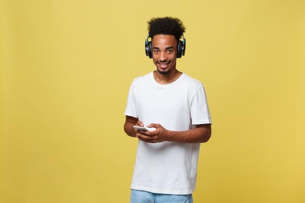 Jonge zwarte man luisteren naar muziek via zijn koptelefoon. geïsoleerd op gele achtergrond.