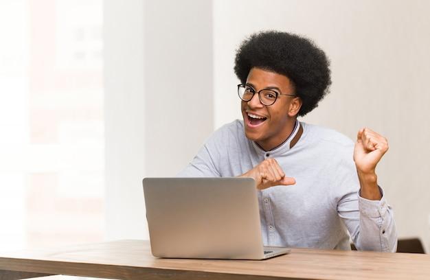 Jonge zwarte man met behulp van zijn laptop dansen en plezier maken