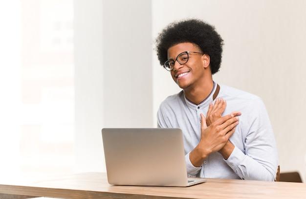 Jonge zwarte man met behulp van zijn laptop doet een romantisch gebaar