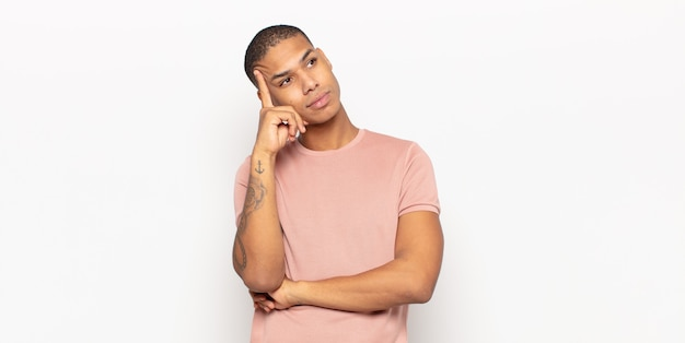 Jonge zwarte man met een geconcentreerde blik, zich afvragend met een twijfelachtige uitdrukking, opkijkend en opzij