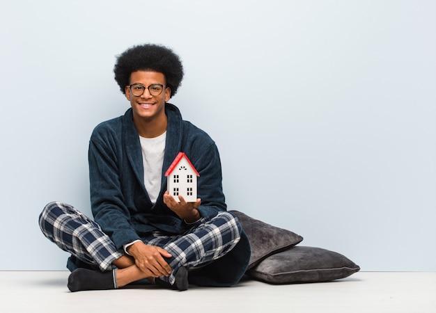 Jonge zwarte man met een huis model zittend op de vloer vrolijk met een grote glimlach