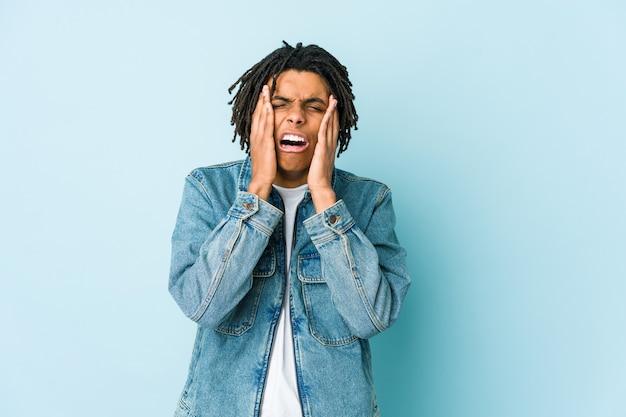 Jonge zwarte man met een jeansjasje troosteloos janken en huilen.
