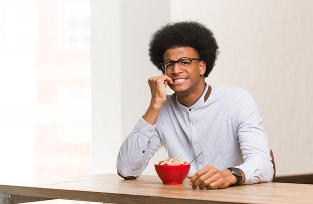 Jonge zwarte man met een ontbijt nagels bijten, nerveus en erg angstig