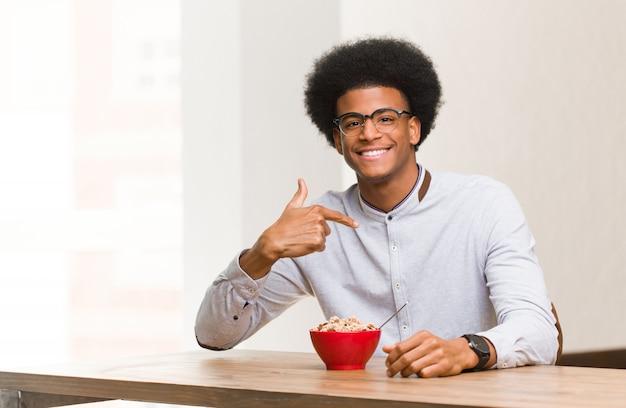 Jonge zwarte man met een ontbijt persoon wijst met de hand naar een shirt kopie ruimte, trots en zelfverzekerd