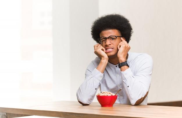 Jonge zwarte man met een ontbijt wanhopig en verdrietig