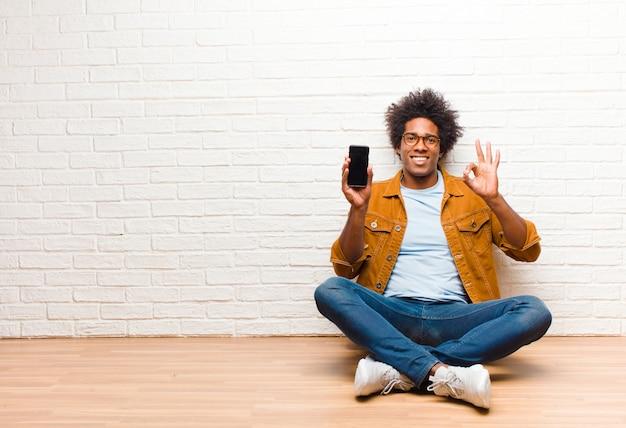 Jonge zwarte man met een slimme telefoon zittend op de vloer
