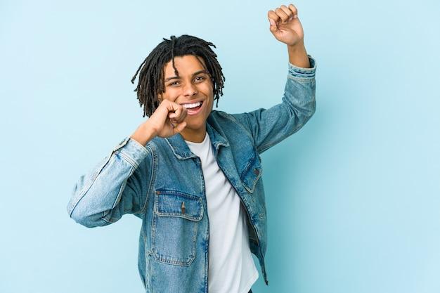 Jonge zwarte man met een spijkerbroek jasje dansen en plezier maken.