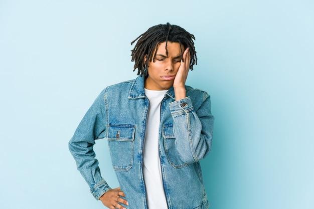 Jonge zwarte man met een spijkerjasje die zich verveelt, vermoeid is en een ontspannende dag nodig heeft.