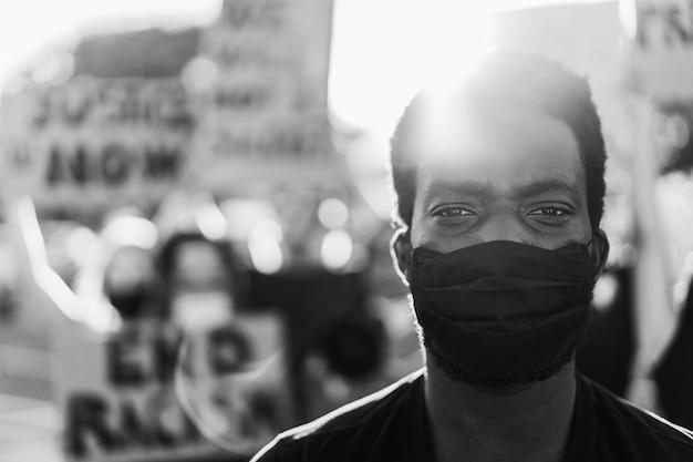 Jonge zwarte man met gezichtsmasker tijdens protest tegen gelijke rechten