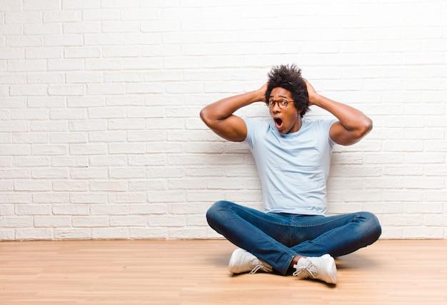 Jonge zwarte man met open mond, met afschuw vervuld en geschokt vanwege een vreselijke fout, terwijl hij zijn handen opheft om thuis op de grond te zitten