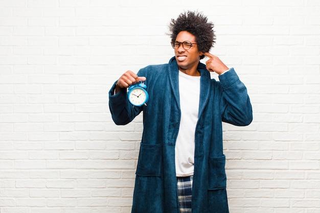 Jonge zwarte man met pyjama met een wekker