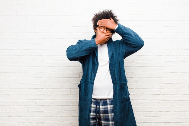 Jonge zwarte man met pyjama met jurk die gezicht bedekt met beide handen nee zeggen tegen de camera! afbeeldingen weigeren of foto's verbieden tegen een bakstenen muur