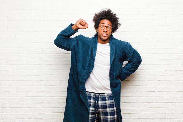 Jonge zwarte man met pyjama met jurk die zich serieus, sterk en opstandig voelt, vuist omhooghoudt, protesteert of vecht voor revolutiebakstenen muur