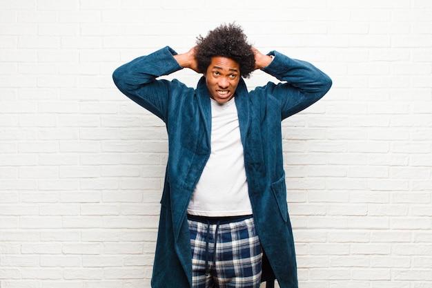 Jonge zwarte man met pyjama met jurk gevoel gestrest, bezorgd, angstig of bang, met handen op het hoofd, in paniek bij vergissing tegen bakstenen muur