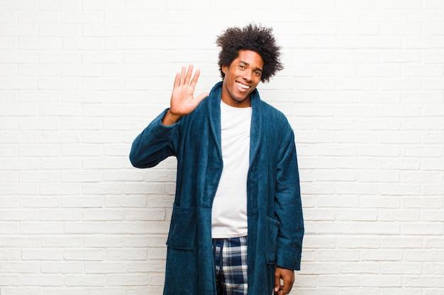 Jonge zwarte man met pyjama met jurk glimlachend gelukkig en vrolijk, zwaaiende hand, verwelkomen en begroeten, of afscheid nemen