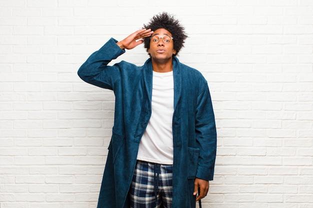 Jonge zwarte man met pyjama met jurk groet de camera met een militaire groet in een daad van eer en patriottisme, met respect